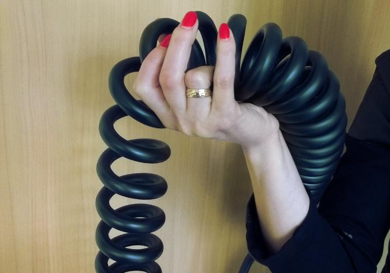 długi kabel spiralny do pojazdów TIR z dłonią dla skali.